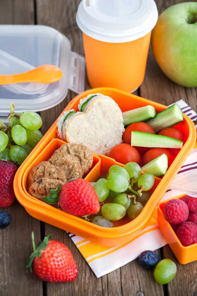 back to school lunch with fruit, sandwhich and drink on table