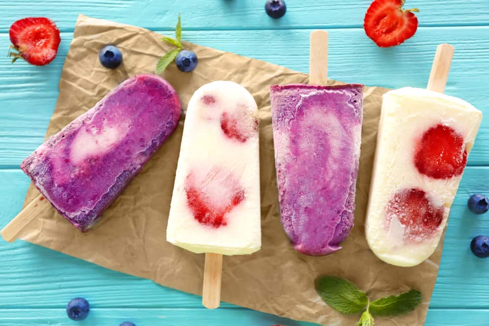 Colorful fruit popsicles on table, closeup