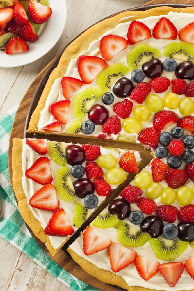 Fruit Pizza with pita bread topped with cream cheese and fruit arranged nicely in a pattern on a table