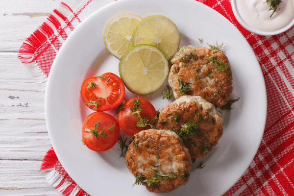 Crabcakes, lemon and tomatoes on white plate on red plaid placemat and wood background