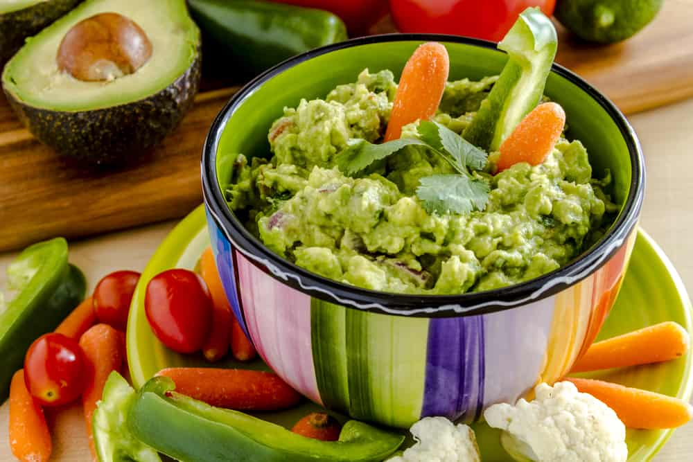Fresh chunky guacamole healthy snack idea in colorful bowl sitting on bright green plate garnished with raw carrots and green peppers and cilantro surrounded by raw vegetables