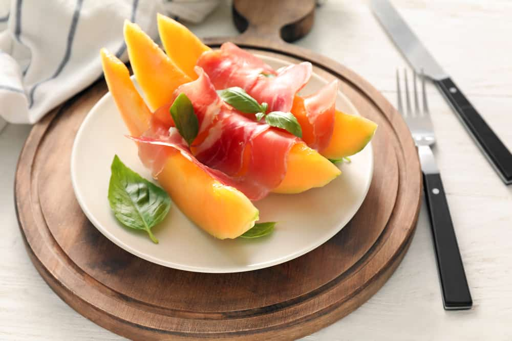 Plate melon and prosciutto healthy snack on wooden board