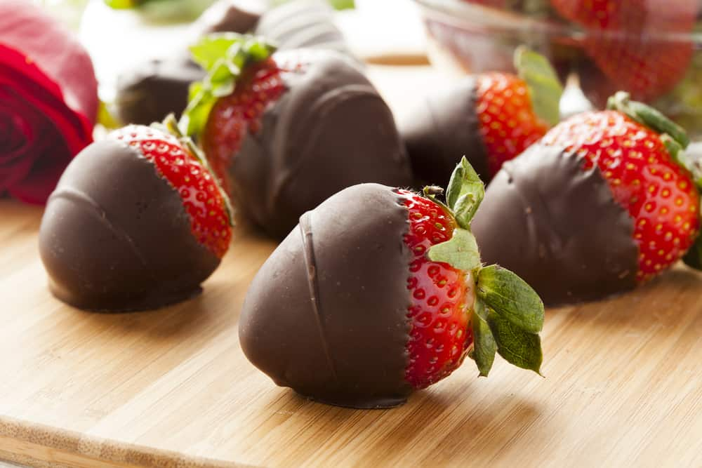 Chocolate covered strawberries on cutting board with bowl in background