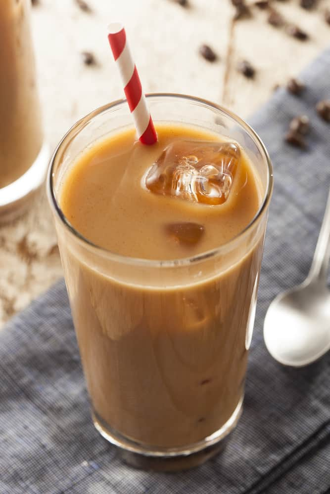Iced Coffee with Cream in glass with red and white straw, coffee beans in background