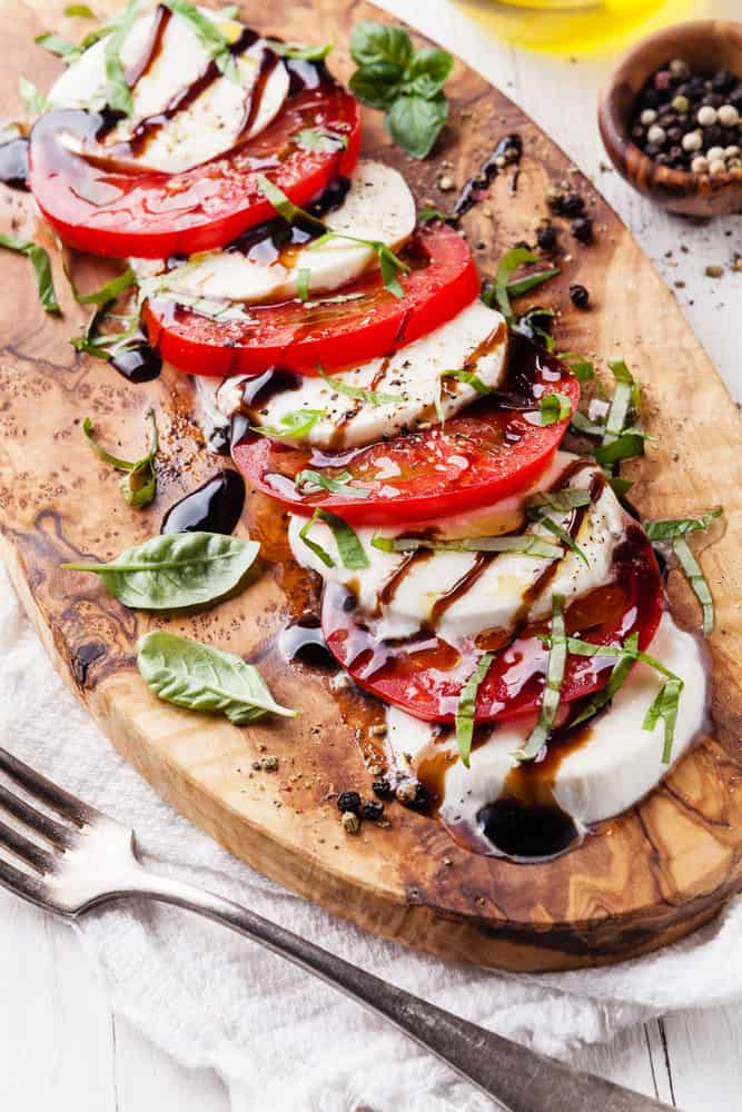 Caprese salad Tomato and mozzarella slices with basil leaves on olive wood cutting board