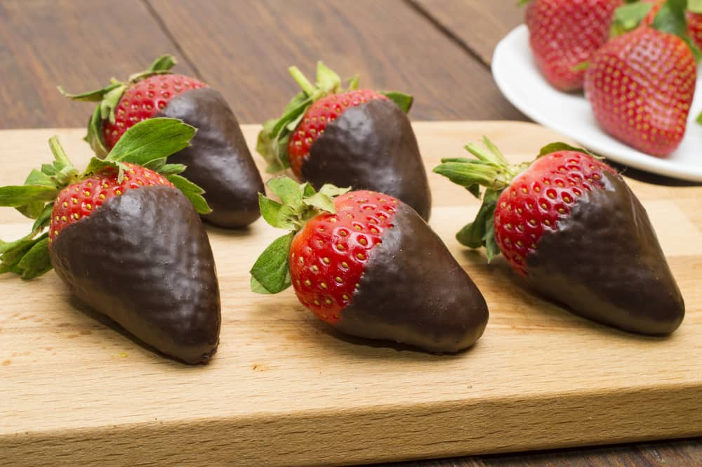 Strawberries dipped in dark chocolate on cutting board, plate of strawberries in background