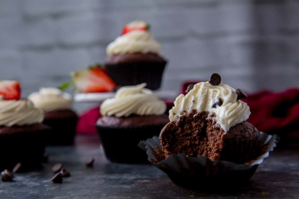 Red Velvet Cupcake desserts with decadent white frosting and topped with a strawberry