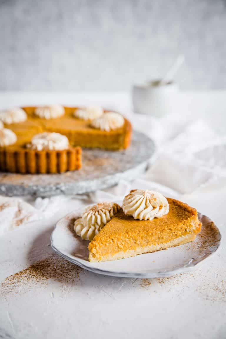 Slice of keto pumpkin pie on plate with whole pie in the background on white plate