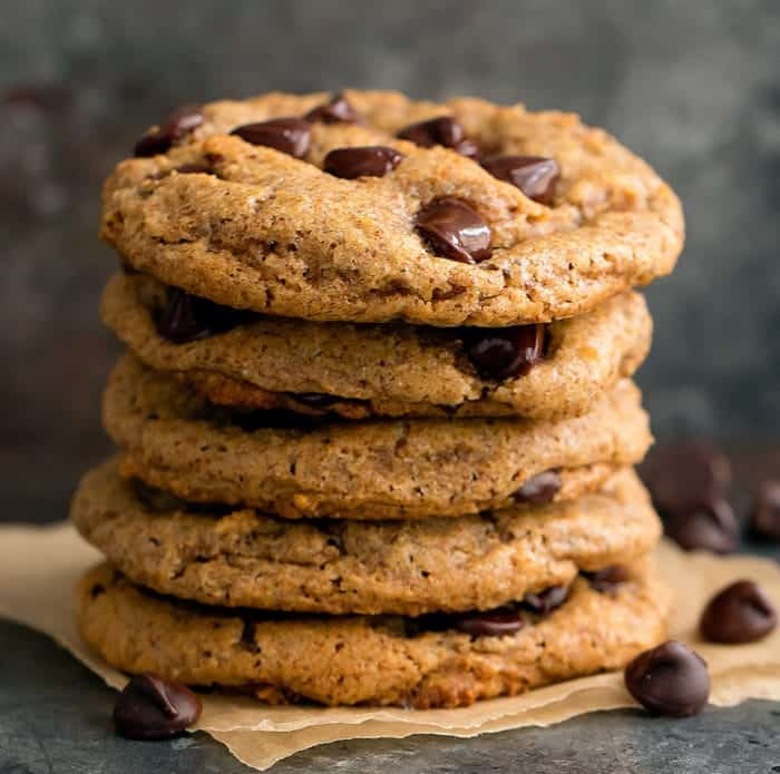 Stack of keto chocolate chip cookies with napkin underneath, chocolate chips spread around on side of cookies