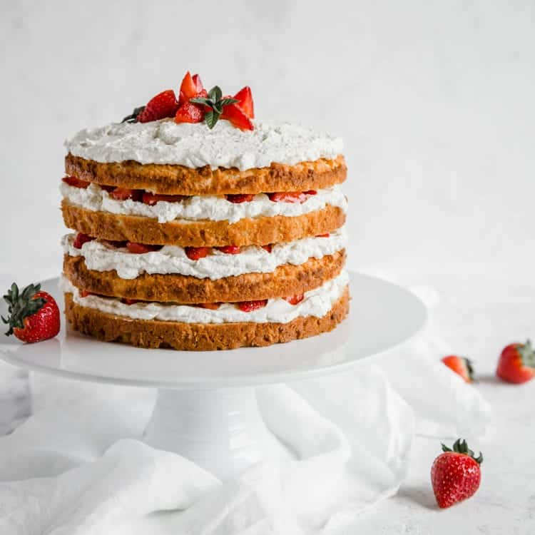 Strawberry shortcake with four layers on white cake plate, strawberries in background