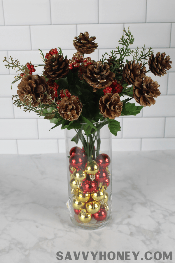 Vase with ornaments and pinecone Christmas centerpiece
