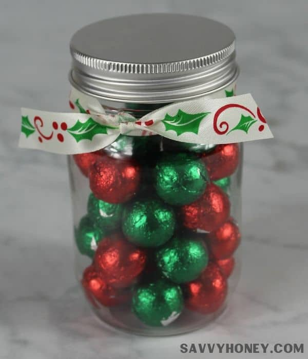 Mini mason jar filled with red and green holiday candy with holly bow