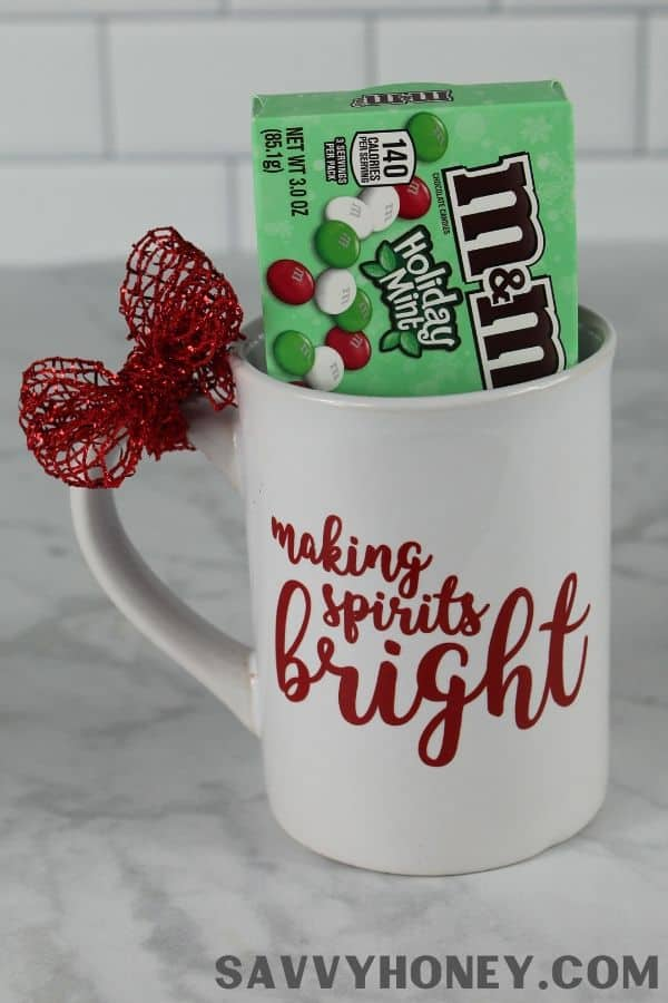 "Dollar Tree Mug Christmas gift idea with a box of m&m's and a red bow around mug that reads ""making spirits bright"""