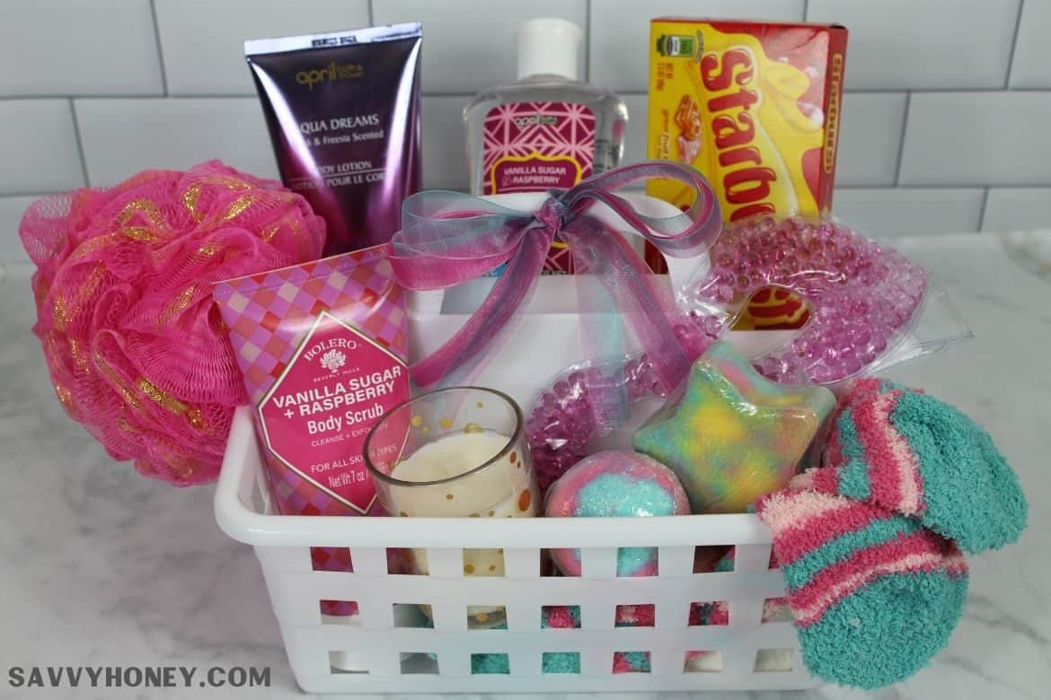 Dollar Tree Spa basket with pampering lotion, bubble bath, candy, candles, bath bombs, socks and bath puff in white Dollar Store container with bow