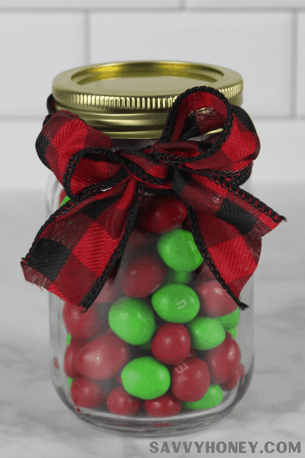 Mason jar with candy and ribbon wrapped around it