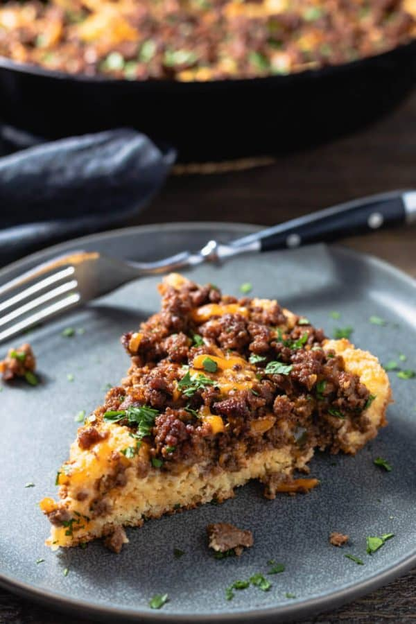 Piece of sloppy joe casserole on a grey plate with fork and skillet in background