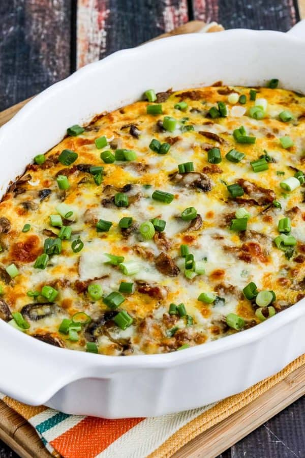 Low Carb breakfast casserole in white dish with sprinkled green onions on top of colorful placemat