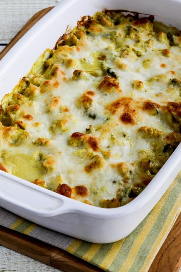 Casserole in white dish topped with cheese on green and yellow striped placemat