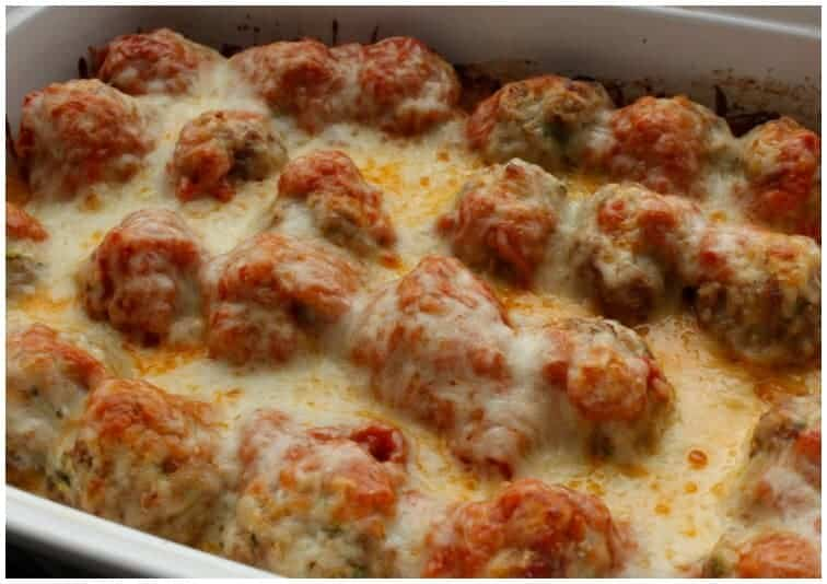 Meatballs with cheese on top in a white casserole dish