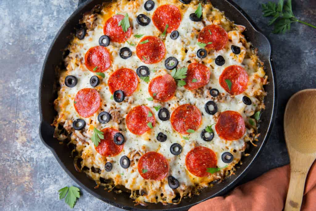 Black skillet filled with low carb pizza casserole topped with pepperoni and olives. Wooden spoon in background