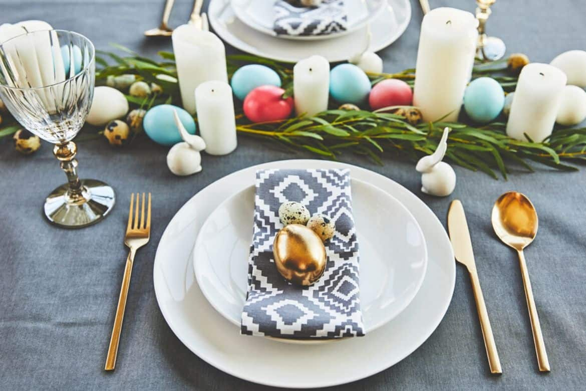 Easter table setting, white plate with gold egg on top, silverware, with greenery and colorful eggs and white candles along table