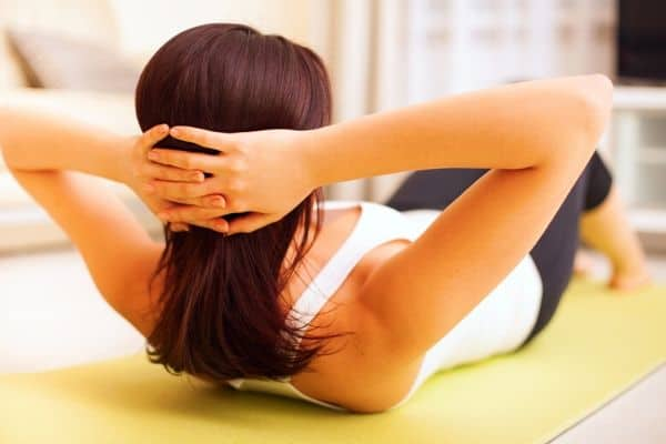Woman doing at home workout of crunches on yellow mat