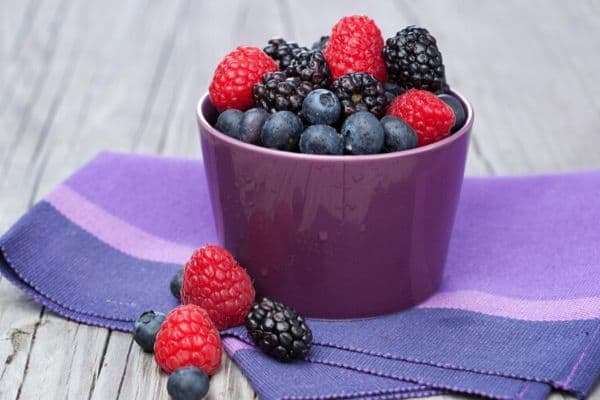 Purple bowl of berries with purple towel underneath