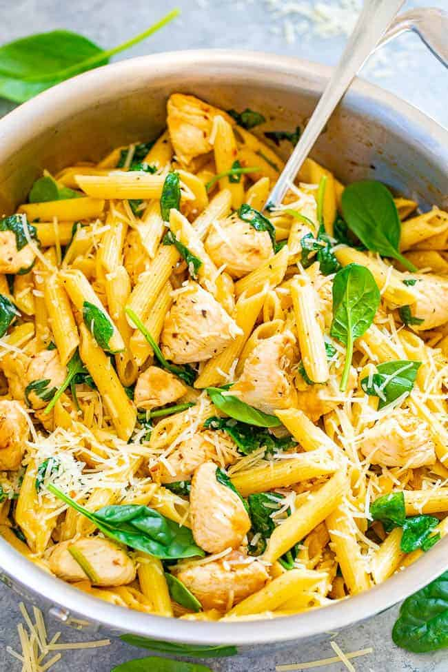 bowl of pasta topped with spinach in white bowl