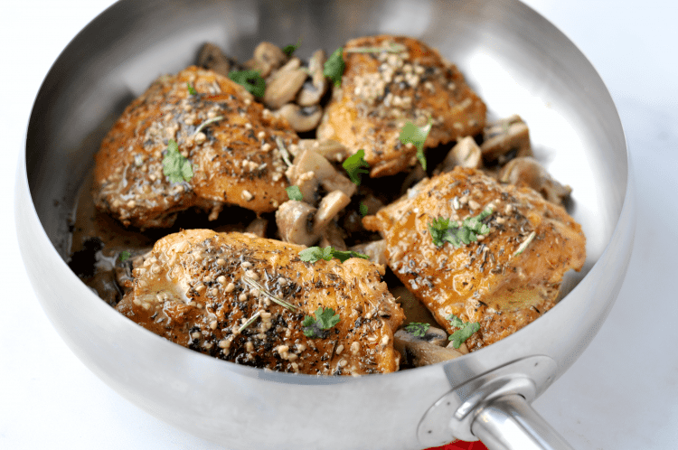 chicken and mushrooms in silver skillet pan