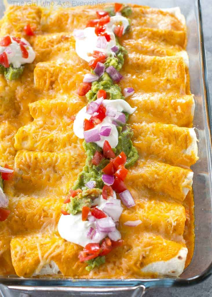 Enchiladas in a glass casserole dish topped with sour cream
