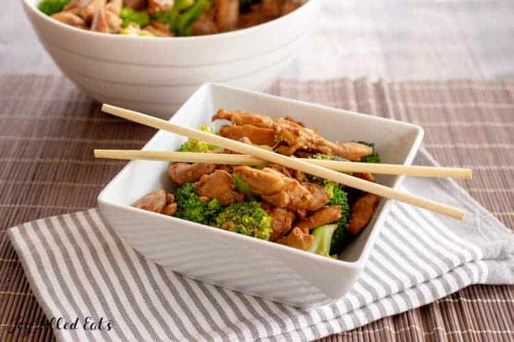 Keto chicken teriyaki served over broccoli in a square white dish with chopsticks