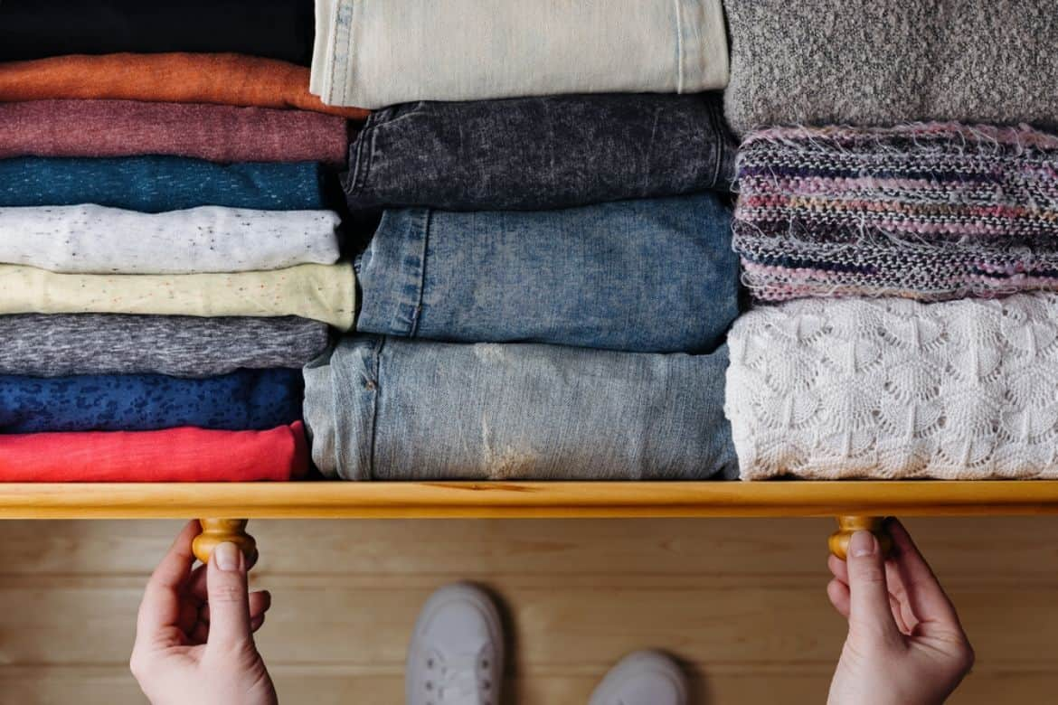 drawer with neatly folded clothes, woman pulling out drawer