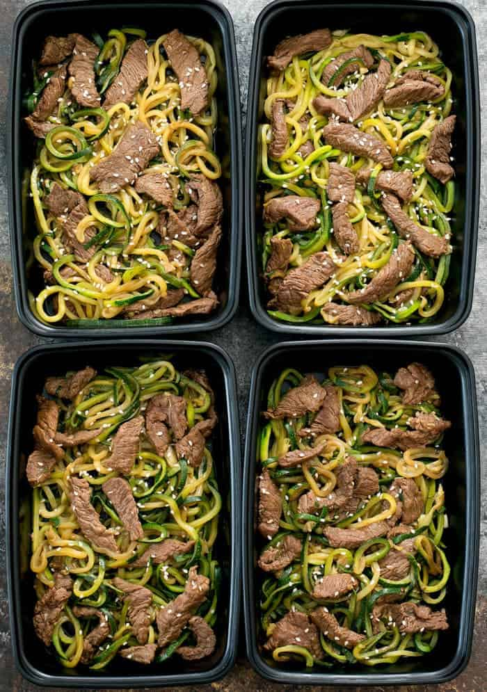 Garlic Beef over zucchini noodles in black meal prep containers