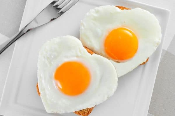 heart shaped sunny side up eggs on toast on white plate with fork in background