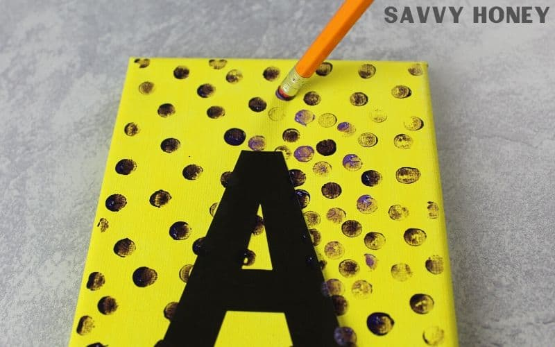 "DIY Canvas Wall Art, pencil making purple dots on yellow canvas, inital ""A"" on canvas"