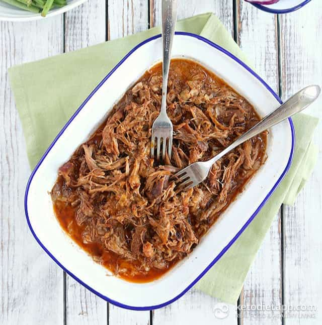 Keto pulled pork in white casserole dish with blue trim, two forks dipping into the pulled pork, dish on green napkin with wood background