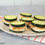 Keto Cucumber sandwiches with cream cheese and turkey on white plate, white and pink striped towel underneath plate and grey cement background
