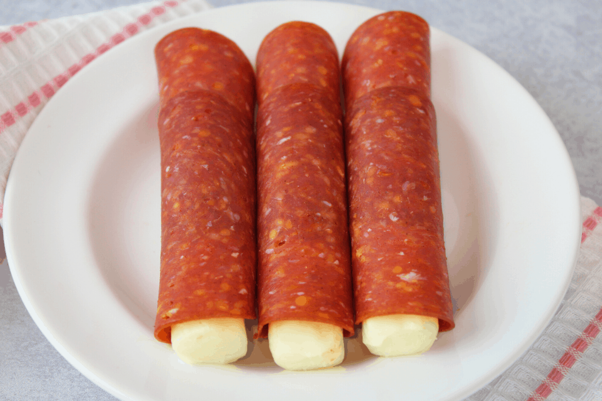 Keto Roll Ups (Pepperoni slices wrapped around string cheese) on white plate with coral and white striped napkin underneath plate, grey concrete background