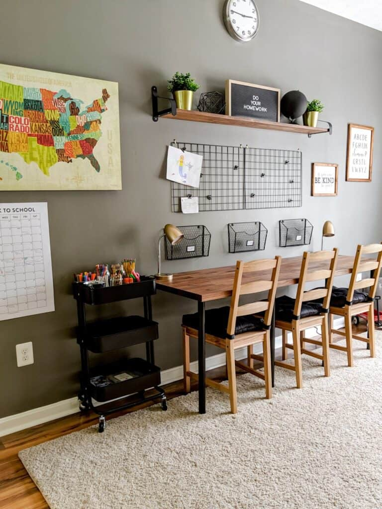 Organized homeschool room with grey walls, map and framed pictures on the wall, homework work station consisting of a desk, chairs and storage baskets  mounted to the wall