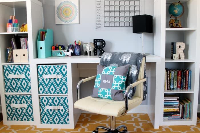 Homeschool desk that is white with lots of storage cubbies. Books, knick knacks,and supplies in cubbies and on desk. Cream colored office chair in front of the desk with a colorful pillow