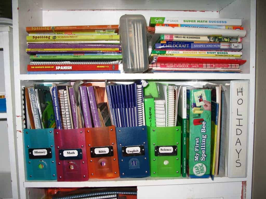 Organized homeschool textbooks and materials on a white bookshelf with brightly colored labeled bins organizing binders, worksheets and homeschool curriculum