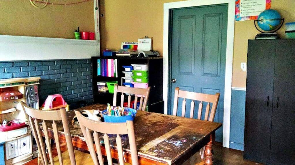 Simple homeschooling room with wooden table and chairs, tall black storage cabinet in right side of the room, blue door and kids toys in the left hand corner of the room