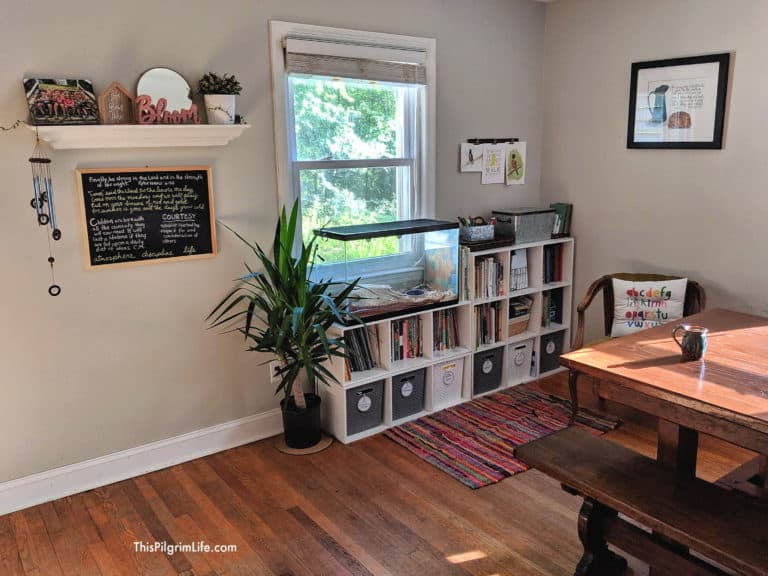 Homeschooling organizing idea for small spaces with storage cubbies against the window. Cubbies organize homeschool books and leaning materials, plant next to storage unit, small chalkboard on wall, dining room table in the front