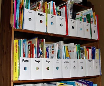 Homeschool library organization separated with white magazine holders with subject labels. Books filling each magazine holder.