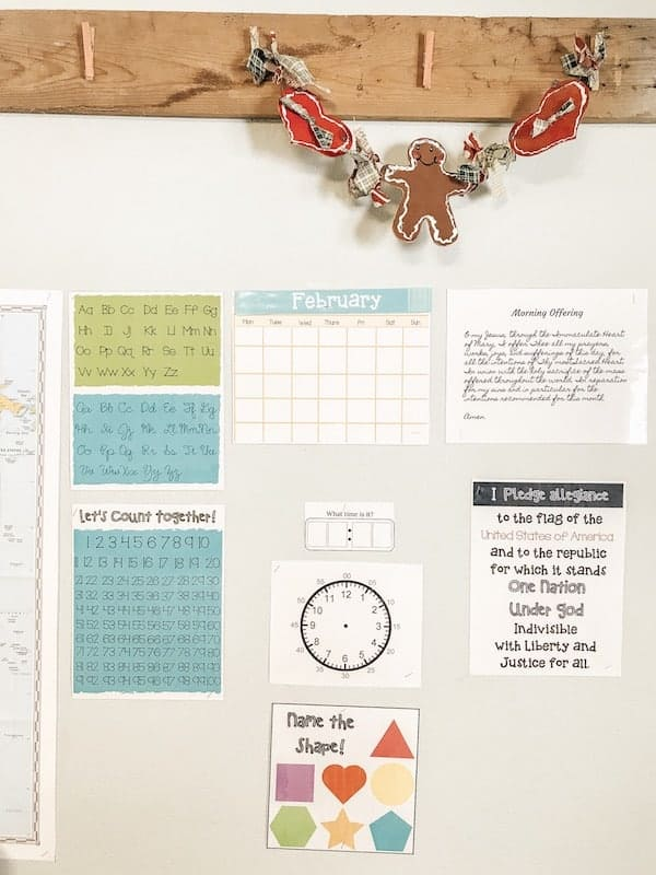 Homeschool morning board with different signs and learning materials hanging on the wall, hooks on the wall with a decorative wall hanging