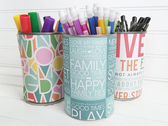 DIY homeschooling project showcasing three soup cans that have been covered in colorful scrapbook paper storing pens, markers, etc. on a white wooden background