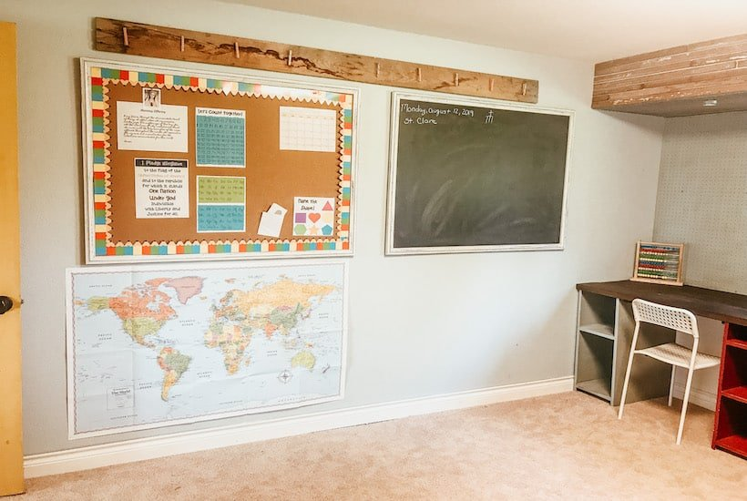 Homeschooling room that has a front wall with a hanging chalkboard, bulletin board and map. Wood detail on the top of the wall. In the corner of the homeschooling space there is a kids desk with built in red and grey storage cubbies