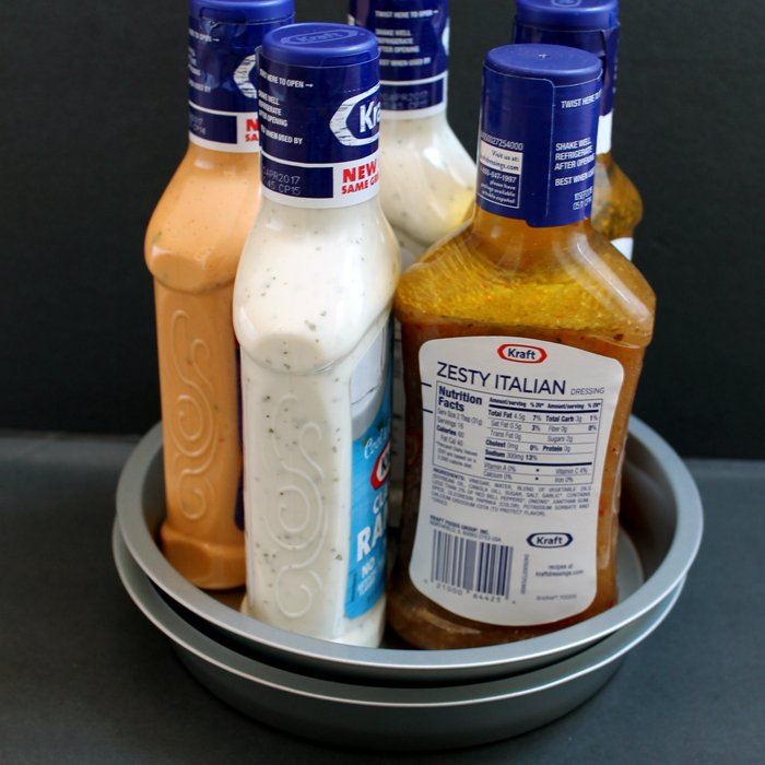 dollar tree diy kitchen organization lazy susan project, two pans with five dressing bottles inside, grey background