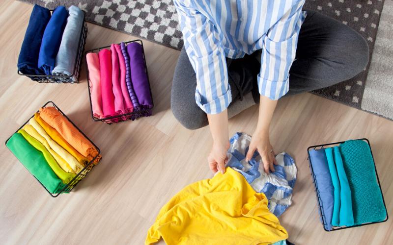 Dollar Store storage baskets with colorful clothing organized inside, woman folding clothing sitting on grey rug