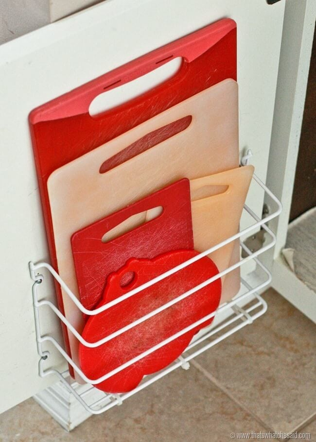 dollar tree kitchen storage white rack mounted to white cabinet with red and wood cutting boards organized inside